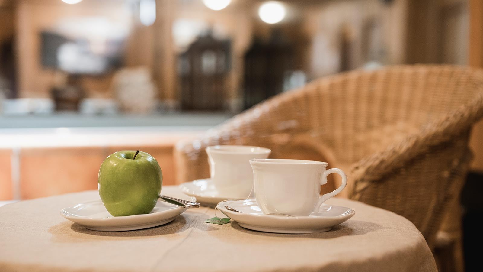 Detail of two cups of tea and a green apple at Hotel in Arabba with wellness center